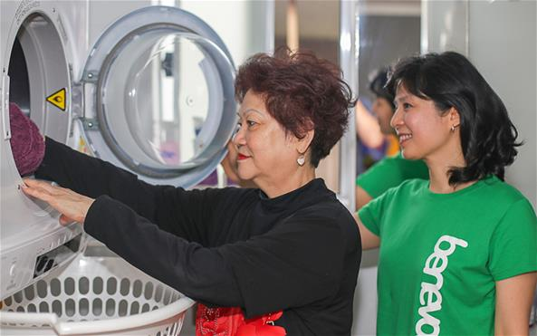 A Benevolent Society staff assisting a client with her laundry duties