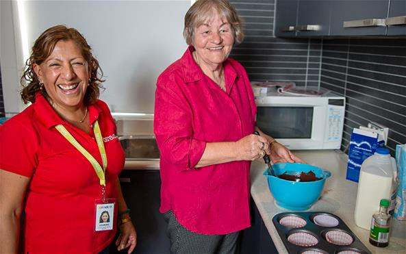 A Benevolent Society staff assisting a senior client with baking cupcakes