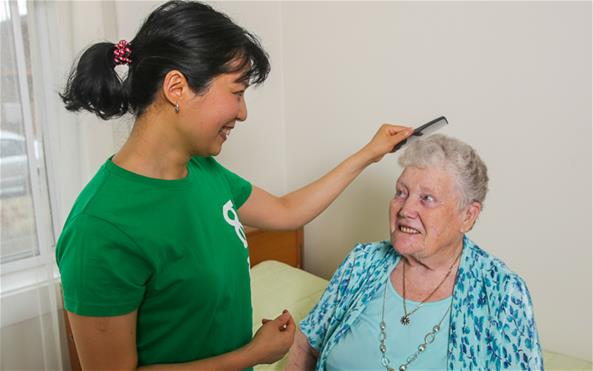 A Benevolent Society staff assisting a senior client with her personal care