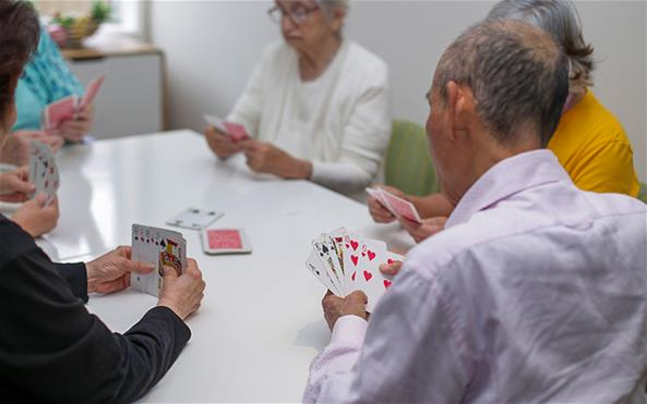 A group of senior clients of the Benevolent Society playing cards