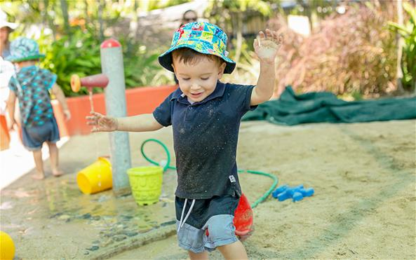 Young boy with a colorful sun hat at playground
