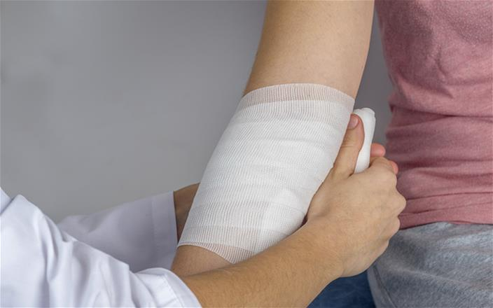 A bandage being applied to s person's forearm