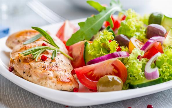 A tasty and healthy-looking cooked piece of chicken with a fresh salad on a plate