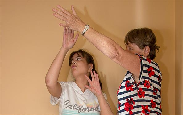 A person with autism performing an arm exercise with her physiotherapist