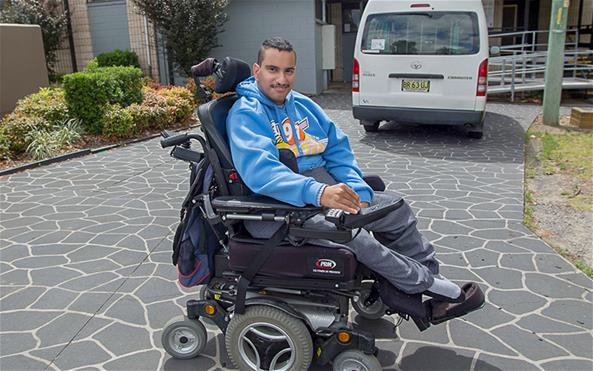 The Benevolent Society client Gaith in a new wheelchair in front of his house