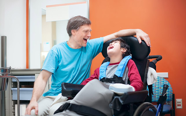 A boy with disability smiling with his carer