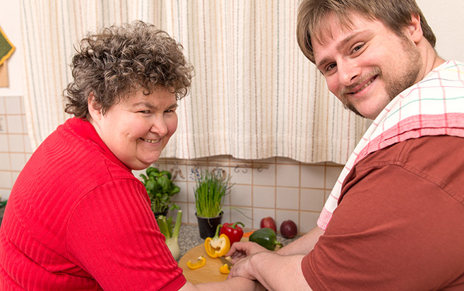 Man with disability preparing food in the kitchen with his mother