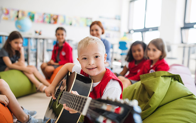 Boy playing guitar in music therapy class