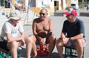 A photograph of 3 men sitting on the bondi beach esplanade having a chat