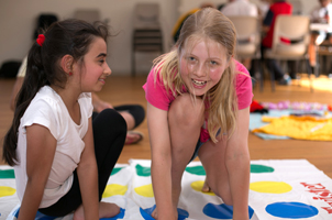 A photo of 2 girls playing twister