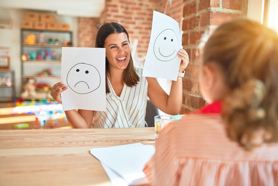 A therapist smiling showing a child mood cards