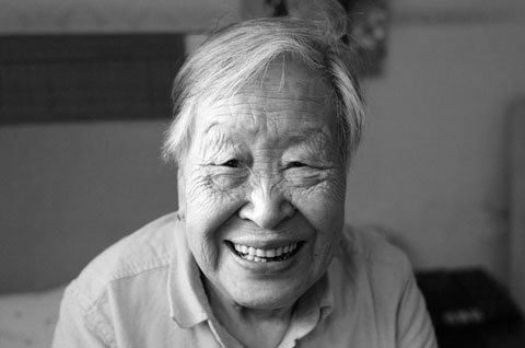A black and while close up portrait photo of an elderly woman smilin