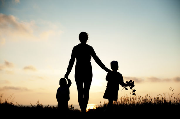 Photo of a silhouette of a woman holding the hands of her 2 children