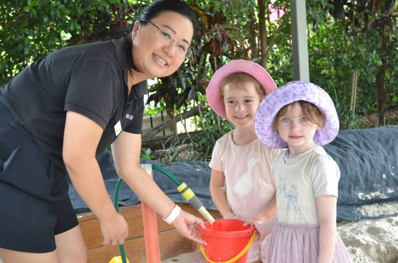 Phobe smiling and helping children at Benevolent Society Kindergarten
