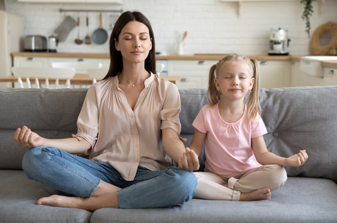 Mother doing a meditation exercise with her young daughter