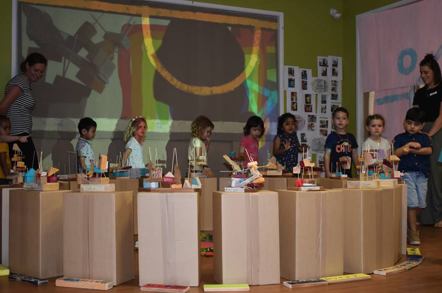 Children walking around and viewing their art exhibition