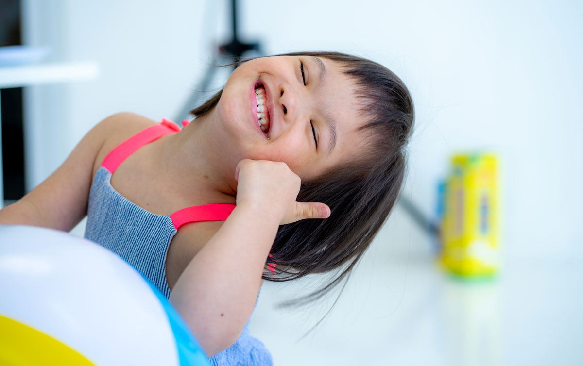 Child smiling and giving thumbs up