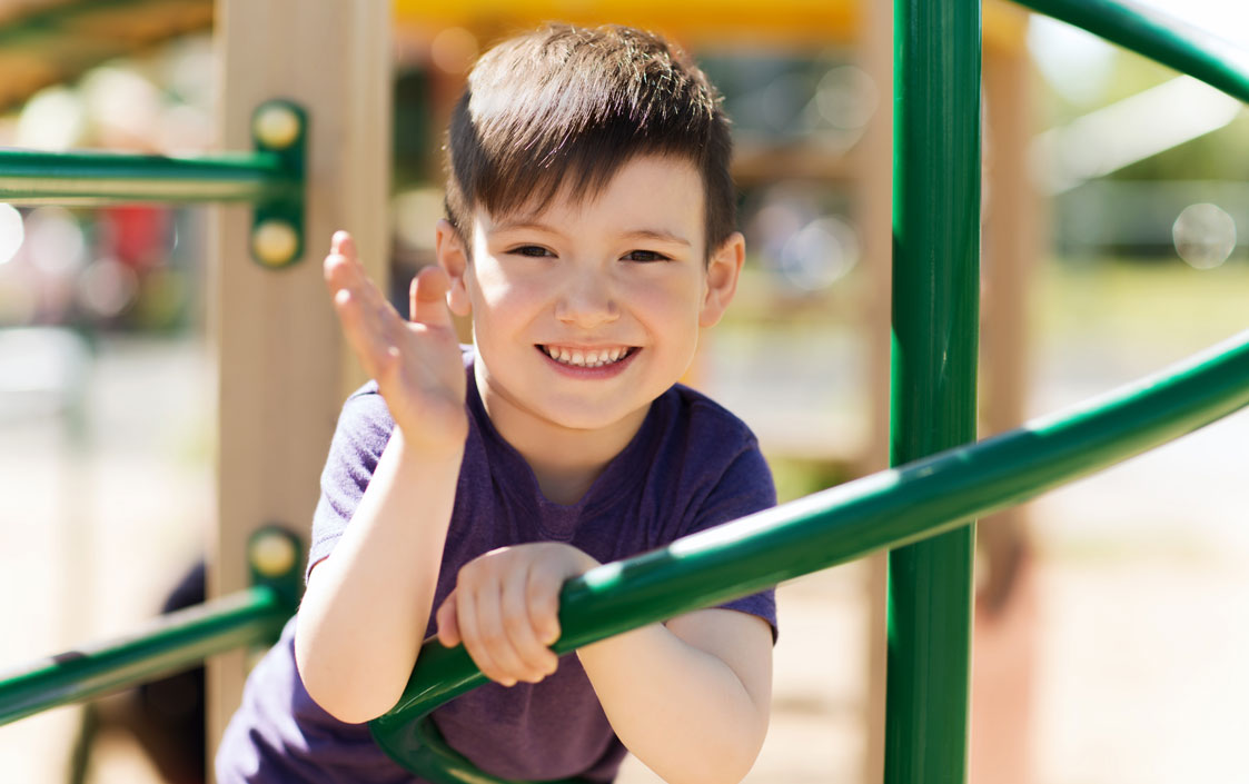 Child smiling on play equipment