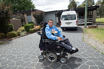 Boy in wheelchair outside his home