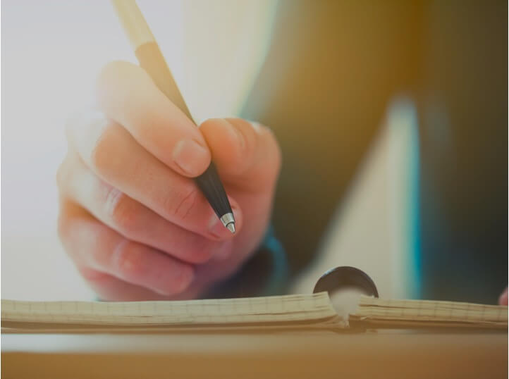 An images of a person writing on a document